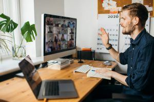 Young man having Zoom video call via a computer in the home office